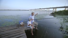 Happy family, male parent and his little boy in straw hats have fun talking fishing on pier near the river during the stock footage