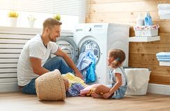 Happy family man father householder and child   in laundry with. Happy family men father  householder and child daughter in laundry with washing machine Stock Photos