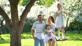 Happy family man kissing woman and their girls swing in spring season garden stock video footage
