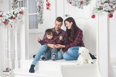 Happy family man woman and child sitting on porch of christmas d royalty free stock images