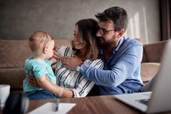 Happy family-man and woman spending happy time at home with their baby son and playing together. Happy family-young men and women spending happy time at home stock images