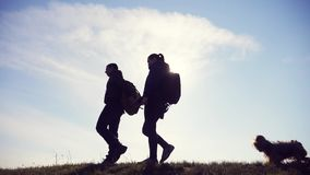 Happy family man and woman teamwork walking go hand in hand silhouette of tourists on top of mountain sunlight. couple. Man lifestyle and girl with backpacks stock video footage