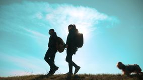 Happy family man and woman teamwork walking go hand in hand silhouette of tourists on top of mountain sunlight. couple. Man and lifestyle girl with backpacks stock video footage