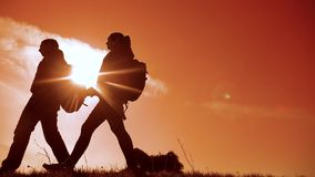 Happy family man and woman teamwork walking go hand in hand silhouette of tourists on top of mountain sunlight. couple. Man and girl with backpacks and stock video footage
