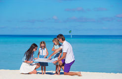 Happy family with map on the beach Stock Photos