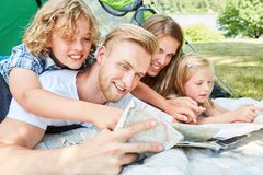 Happy family with map while camping. In front of the tent in the summer holidays stock photo