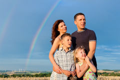 Happy family on a meadow in front of rainbow. Happy family - mother, father, children - standing under a Rainbow in summer looking into a glorious future Royalty Free Stock Images