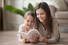 Happy family mom baby sitter and kid daughter reading book. Happy family mom baby sitter and cute kid daughter having fun with book lying on warm floor, smiling stock photos