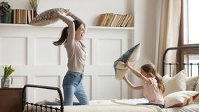 Happy mom and kid daughter having pillow fight on bed. Happy family mom baby sitter and little kid daughter having fun pillow fight on bed, young mother nanny stock photography