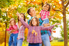 Happy family with mom and dad carry little girls. And older daughter throw maple leaves royalty free stock photo