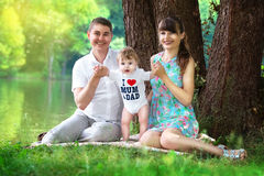 Happy family, mom, dad and little son having fun in the park on. The lake shore background. Summer vacations concept Stock Photography