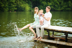 Happy family, mom, dad and little son having fun in the park on. The lake shore background. Summer vacations concept Royalty Free Stock Photography