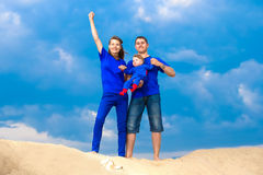 Happy family, mom, dad and little son having fun  in the sand ou. Tdoors against blue sky background. Summer vacations concept Stock Photo