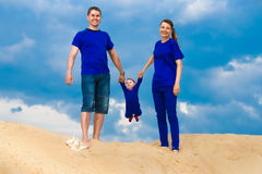 Happy family, mom, dad and little son having fun in the sand ou. Tdoors against blue sky background. Summer vacations concept stock images