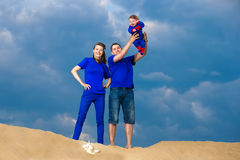 Happy family, mom, dad and little son having fun  in the sand ou. Tdoors against blue sky background. Summer vacations concept Stock Photos