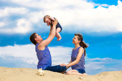 Happy family, mom, dad and little son in striped vests having fu Royalty Free Stock Image