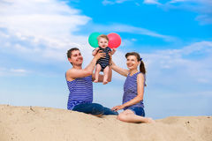 Happy family, mom, dad and little son in striped vests having fu Stock Images