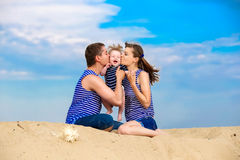 Happy family, mom, dad and little son in striped vests having fu Royalty Free Stock Photography