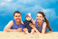 Happy family, mom, dad and little son in striped vests having fu Stock Photo