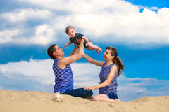 Happy family, mom, dad and little son in striped vests having fu Stock Photos