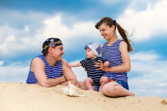 Happy family, mom, dad and little son in striped vests having fu Royalty Free Stock Photo