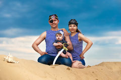 Happy family, mom, dad and little son in striped vests having fu Royalty Free Stock Photos