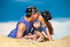 Happy family, mom, dad and little son in striped vests having fun in the sand outdoors against blue sky background. Summer stock photography