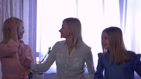 Happy family, mom and daughters fun jumping on bed and then hugging together on camera stock footage