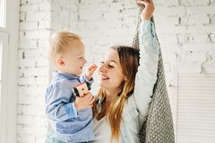 Happy Family Mom and her Cute Son Hugging at Home. Mother and Child Boy Embracing and Having Fun stock photo