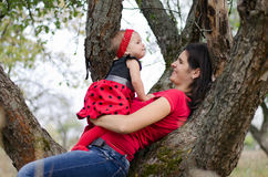 Happy family. Mom and her little daughter lying on the tree in the forest stock images