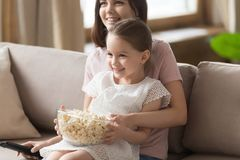 Happy family mom with cute kid daughter watching tv together stock images
