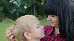 A happy family. Mom with son close-up on the nature. The boy snuggles up to his mother playing games with his mother stock footage