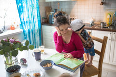 Happy family mom and son  at home kitchen together read book. Caucasian mother,  and son toddler having fun in the kitchen - happy family time, reading book Royalty Free Stock Photo