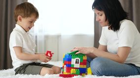 Happy family: mother and son playing with color blocks on white bed at home