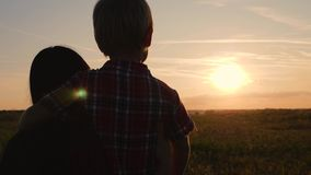 A happy family. Mom and son watching the sunset. Traveling and walking outdoors. The concept of happiness and health.