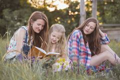 Happy family - mom and two daughters. Are sitting in a meadow and reading a book. Picnic stock image
