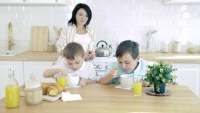 Happy family mom and two sons having breakfast in the kitchen.
