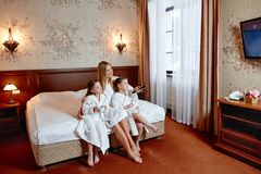 Happy family, mom and two twin girls watching TV. They`re sittin. G on a bed in a hotel room Stock Photography