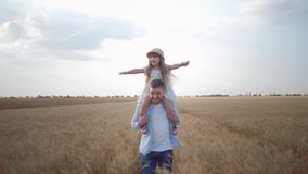 Happy family moments, young father runs with little child girl on his shoulders who screams and rejoices laughing and stock video