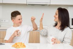 Happy family in the morning. Beautiful women with her son having breakfast in kitchen and smiling royalty free stock images