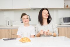 Happy family in the morning. Beautiful women with her son having breakfast in kitchen, listen music and smiling Royalty Free Stock Photography