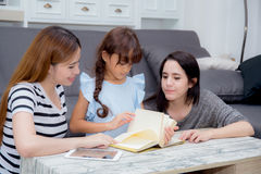 Happy family mother, aunt, freind and daughter teaching read a book. Royalty Free Stock Photos