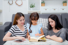 Happy family mother, aunt, freind and daughter teaching read a book. Happy family mother, aunt, freind and daughter teaching read a book at home royalty free stock photography