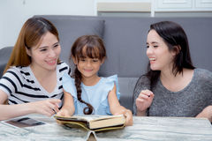 Happy family mother, aunt, freind and daughter teaching read a book. Stock Images