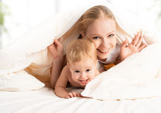 Happy family mother and baby  in bed Royalty Free Stock Photo
