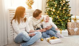 Happy family mother and baby in Christmas morning at Christm. Happy family mother and baby in the Christmas morning at Christmas tree Royalty Free Stock Image