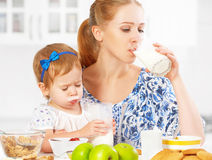 Happy family mother and baby daughter at breakfast: biscuits with milk Royalty Free Stock Image