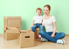 Happy family mother and baby daughter in an empty apartment with cardboard boxes Stock Image