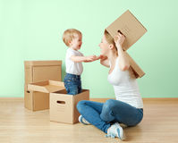 Happy family mother and baby daughter in an empty apartment with cardboard boxes Royalty Free Stock Photo