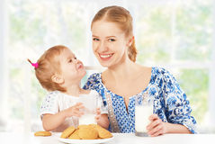 Happy family mother and baby daughter girl at breakfast: biscuit Stock Images